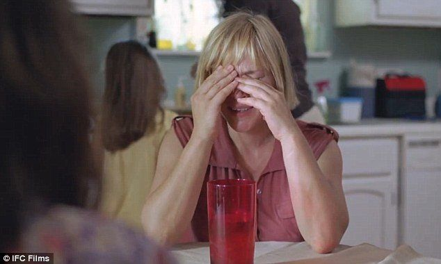 Olivia crying at the kitchen table of a friends\'s after leaving her abusive husband