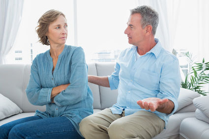"woman looking with contempt at husband with both hands palms up as in ""What did I do?"""