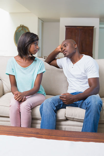 African American couple sitting on a couch seriously discussing issues
