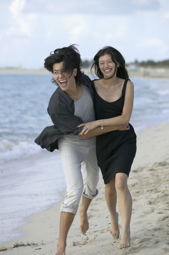 Japanese couple running and laughing on the beach