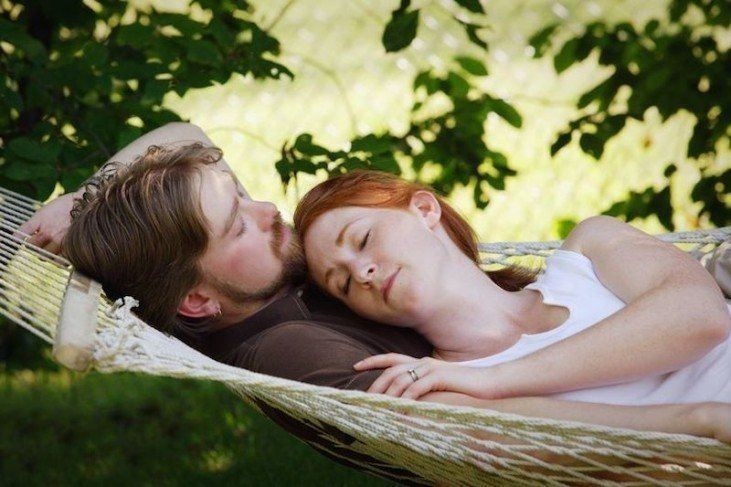 two couples in a hammock laying together sleeping peacefully