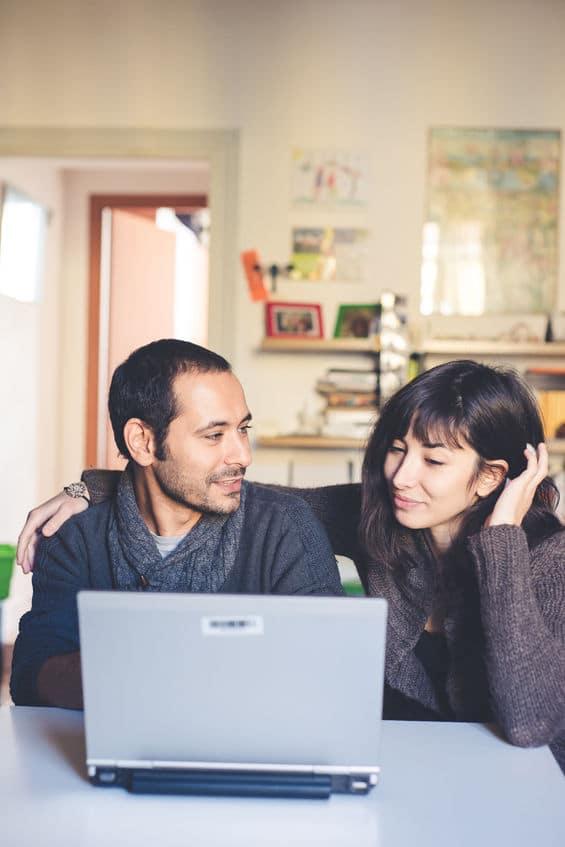 Italian couple on computer, husband talking to wife