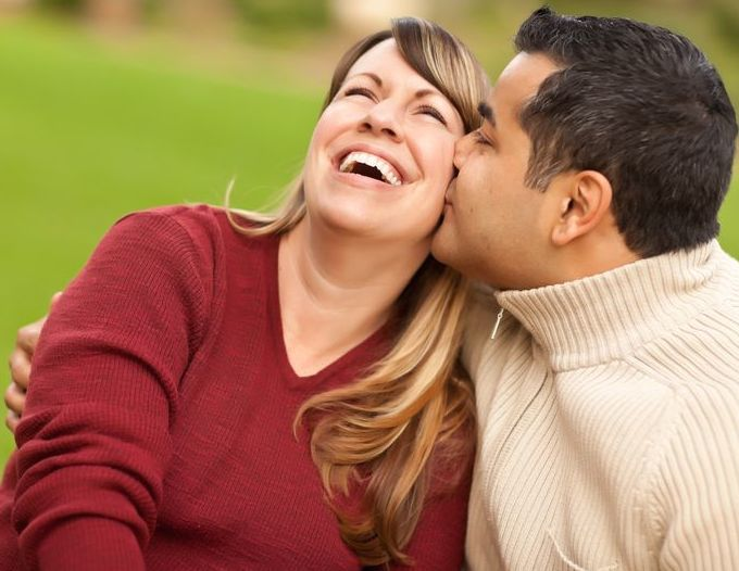 multi-ethnic couple with husband kissing his wife