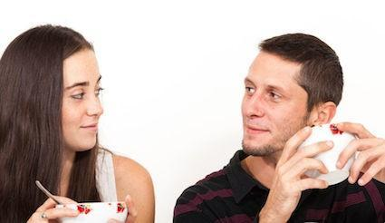 Couple sit eating and looking directly at each other