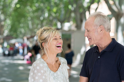Couple in their 50's outside, woman laughing hard, man looking at her smiling