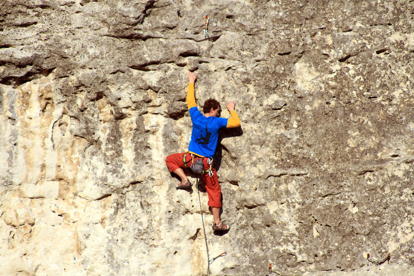 Man is scaling a wall rockclimbing