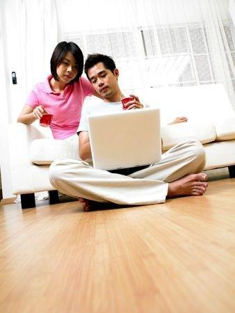asian couple in livingroom doing online marriage counseling