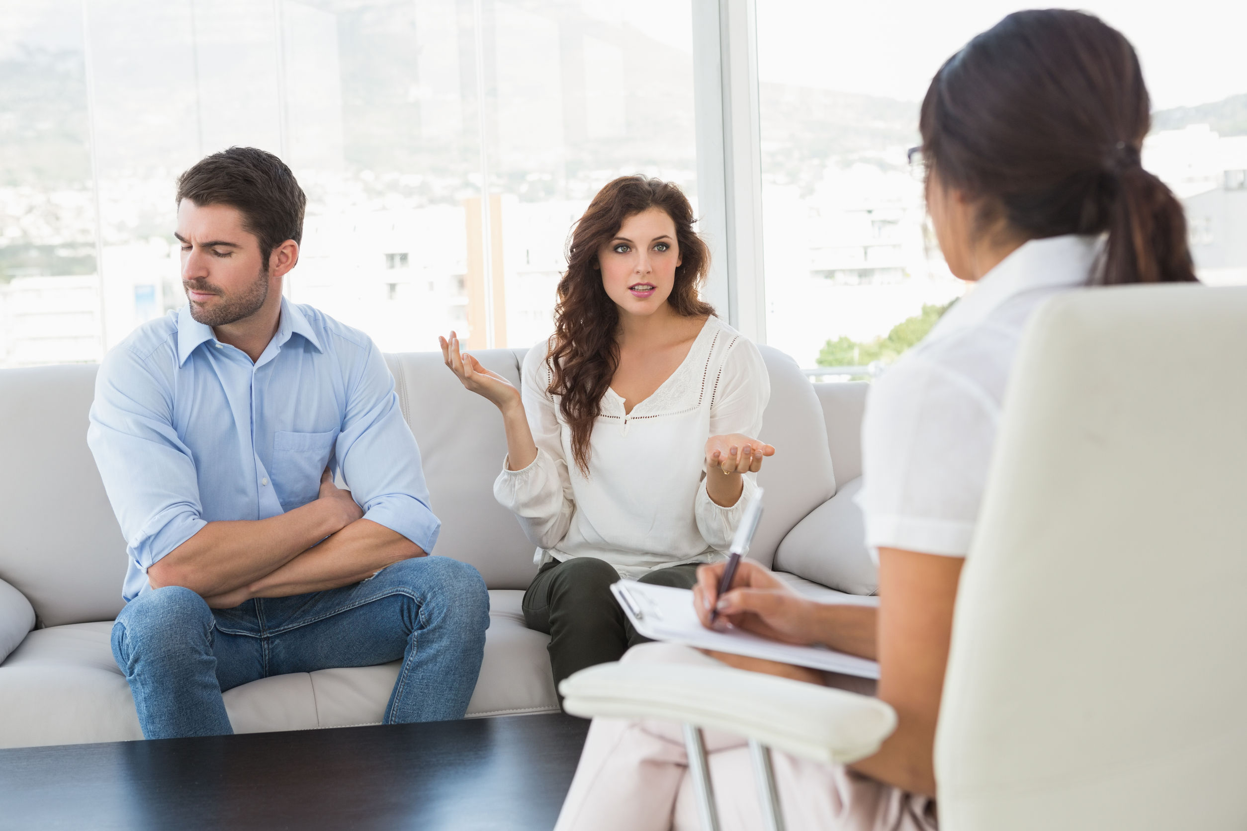 couple quarreling in front of their therapist in the office