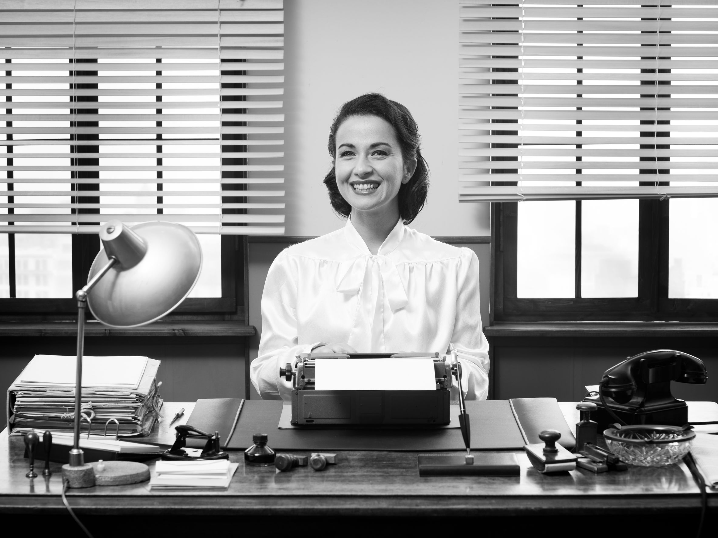 34030162 - cheerful vintage secretary working at office desk and smiling at camera