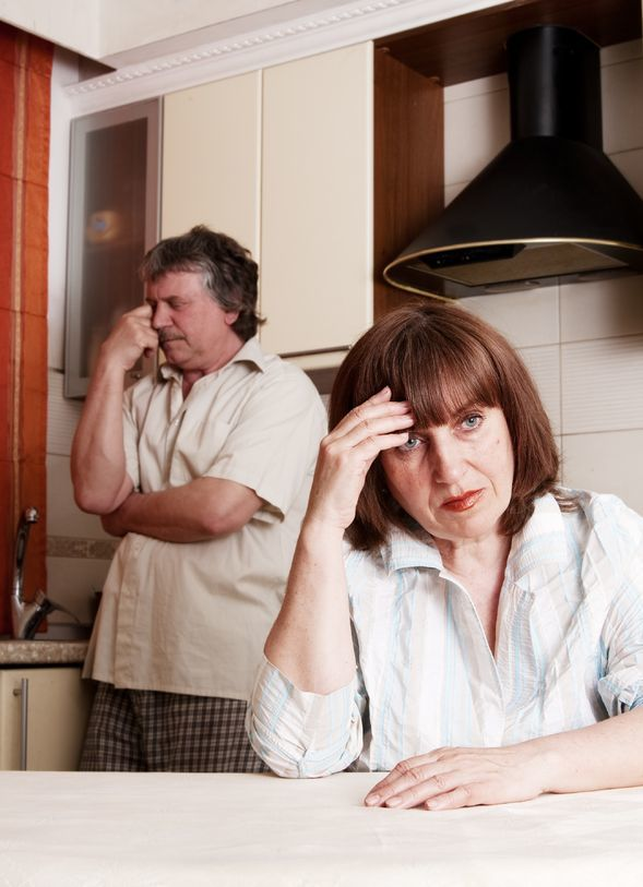 couple in kitchen, husband against the counter with eyes closed and wife at table holding her head starring at camera