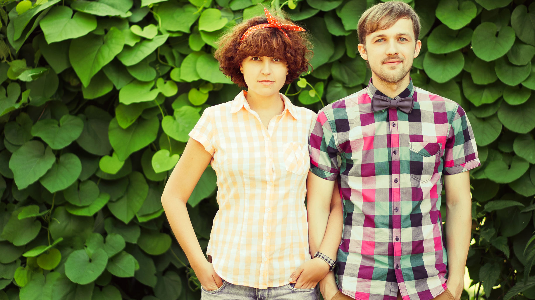 Standing young couple in front of a wall of leaves, looking intently at the camera
