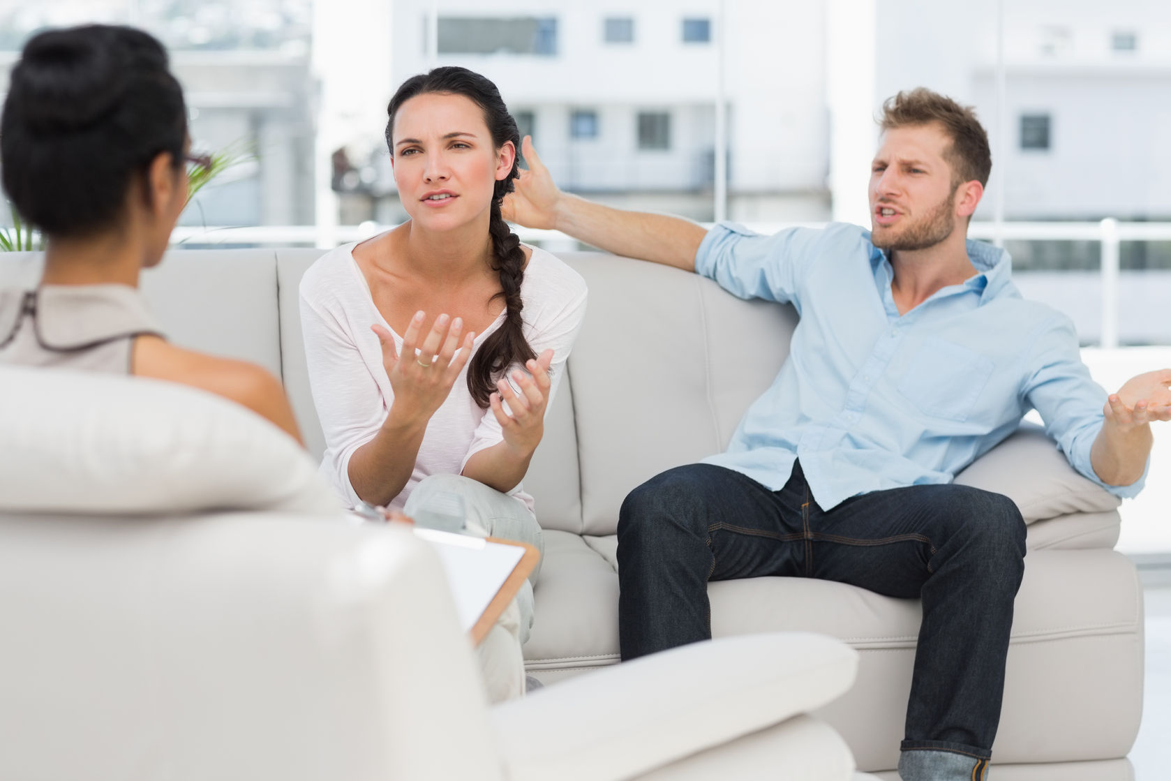 Man explaining to counselor while wife sits pursing her lips