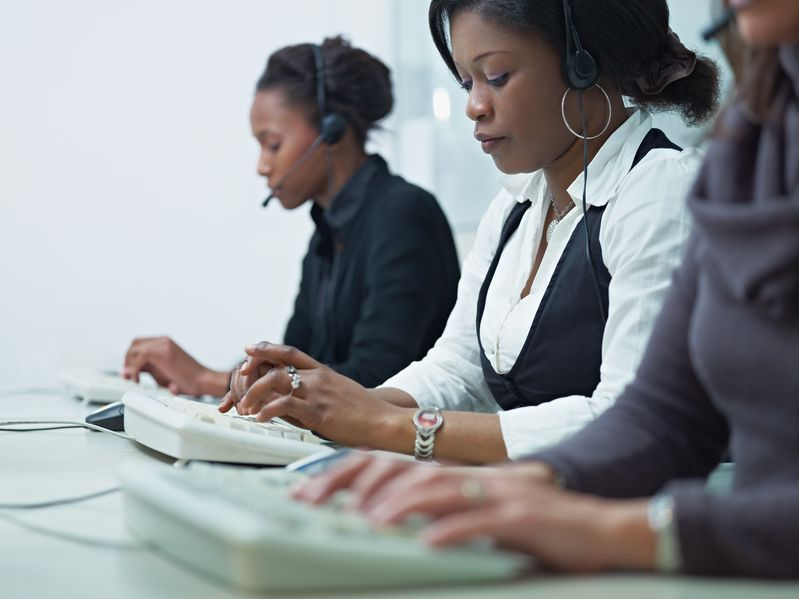 three office staff on computer with headsets