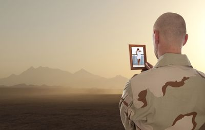 A soldier looks at a picture of his wife while alone in a dusty landscape