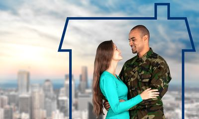 A soldier and his wife stand under the outline of a house