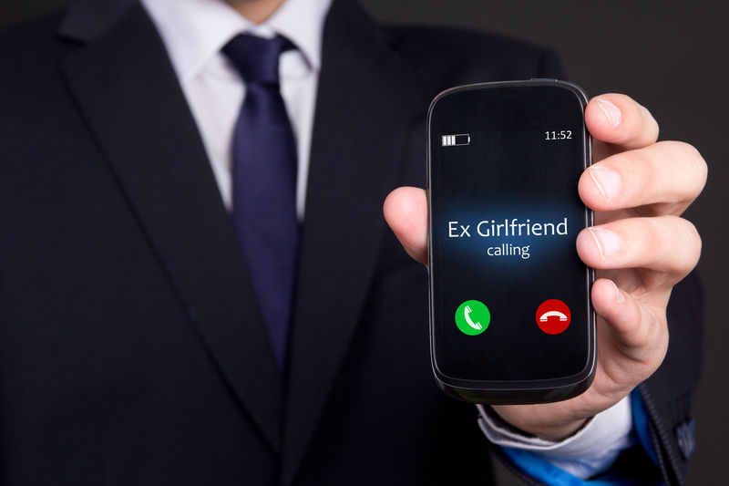 """A man holds a ringing telephone with the caller ID reading """"Ex Girlfriend"""""""