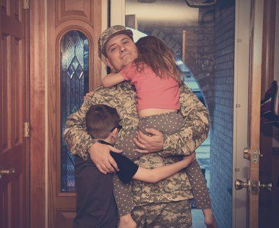 A soldier returns home with his two children hugging him