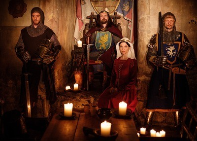 A medieval king flanked by knights and a queen sit in a dimly lit chamber