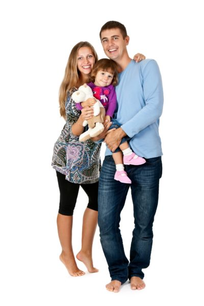 A couple holds their young daughter while smiling