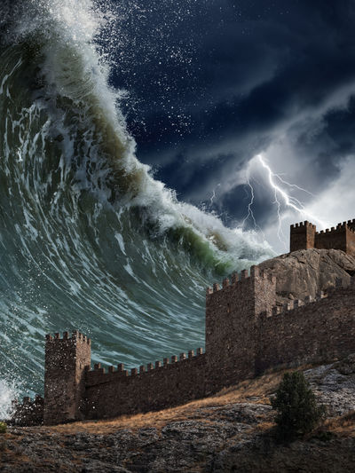 A tidal wave approaches castle walls with a bolt of lightning and dark clouds in the background