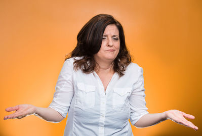 A woman strongly shrugs standing against an orange background
