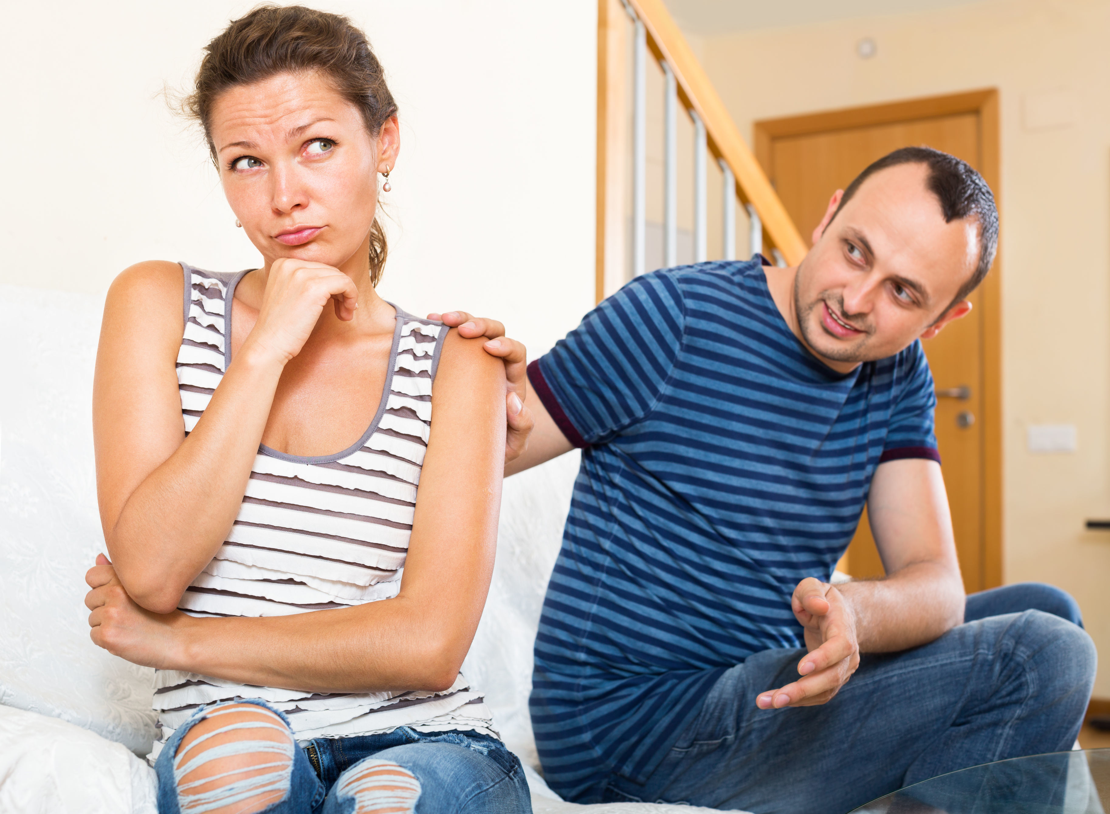 A woman looks away from her husband with a frustrated expression while he attempts to get her attention