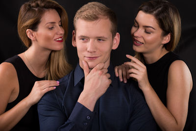 A man with two women caressing his shoulders holds his chin smugly