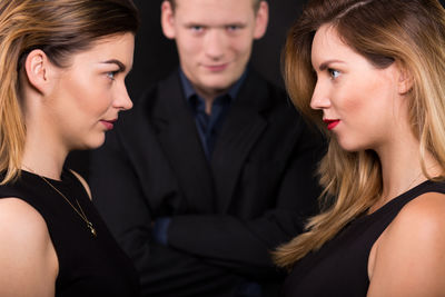 Two women in black dresses look at each other while a man with crossed arms looks on menacingly