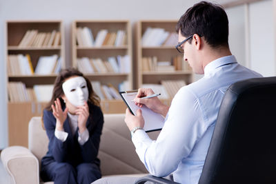 A woman speaks to a therapist while holding a white mask over her face