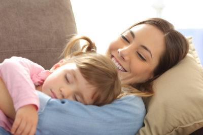 A mother holds her sleeping daughter while smiling